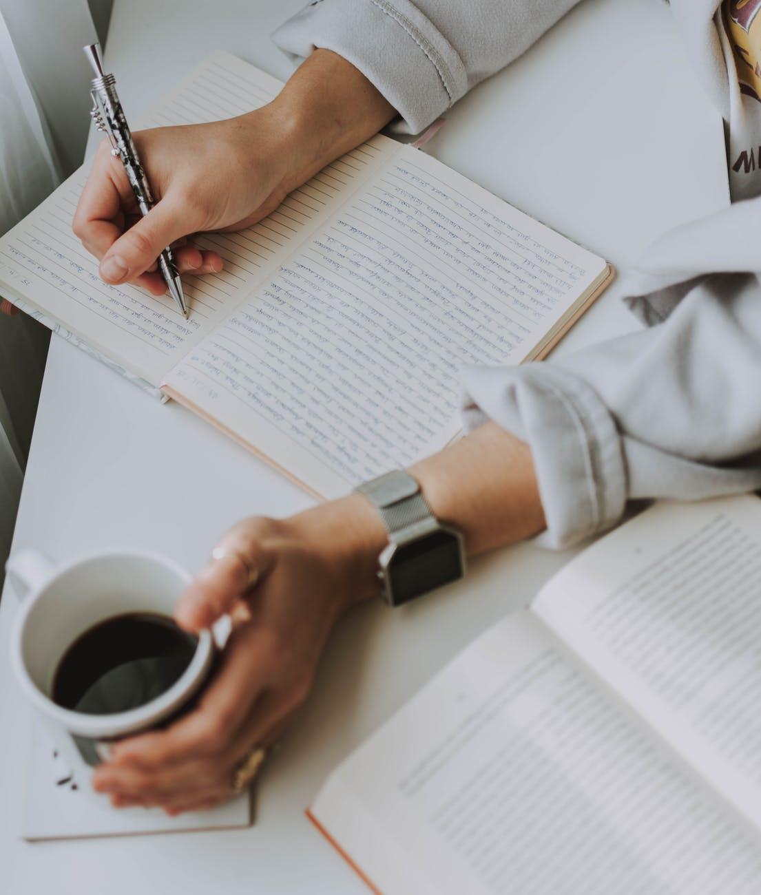 Schreiben auf Papier, Kaffee in der Hand